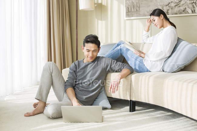 Китайская пара отдыхает дома с ноутбуком и книги — стоковое фото