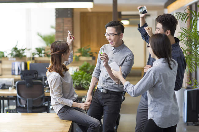 Chinese IT workers celebrating with smartphones in office — Stock Photo