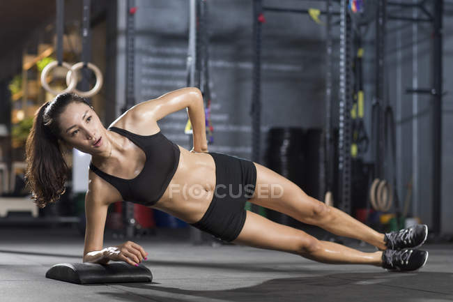 Chinese woman doing side plank exercise — Stock Photo
