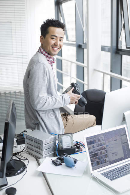 Chinese photographer sitting on desk in office — Stock Photo