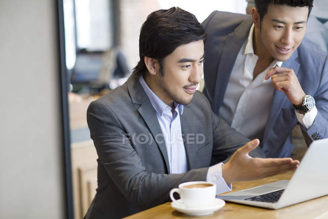Asian men using laptop in cafe — Stock Photo