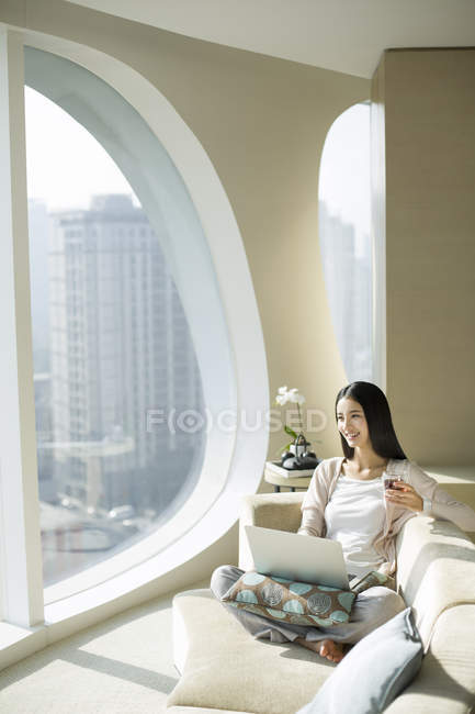Chinese woman sitting with tea cup and laptop on couch — Stock Photo