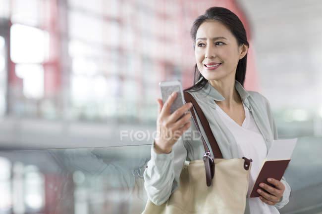 Chinesische Frau mit Smartphone und Ticket am Flughafen — Stockfoto