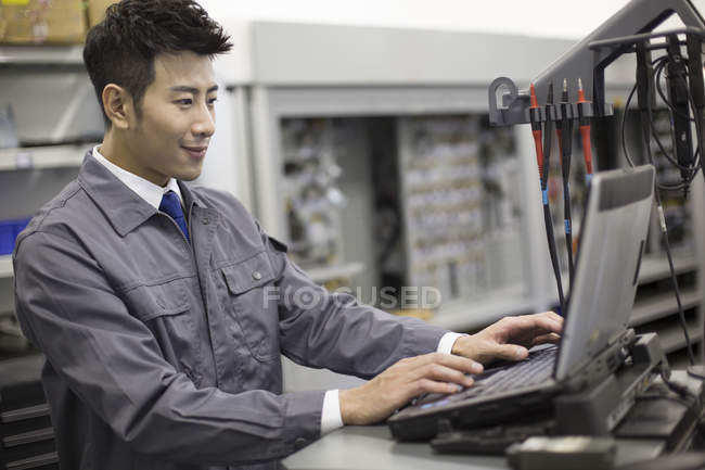 Chinese auto mechanic working with computer in repair shop — Stock Photo