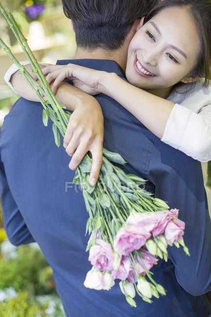 Chinesin umarmt Freund mit Blumen, Nahaufnahme — Stockfoto