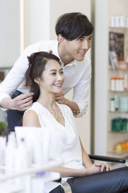 Chinese hairdresser talking with female customer — Stock Photo