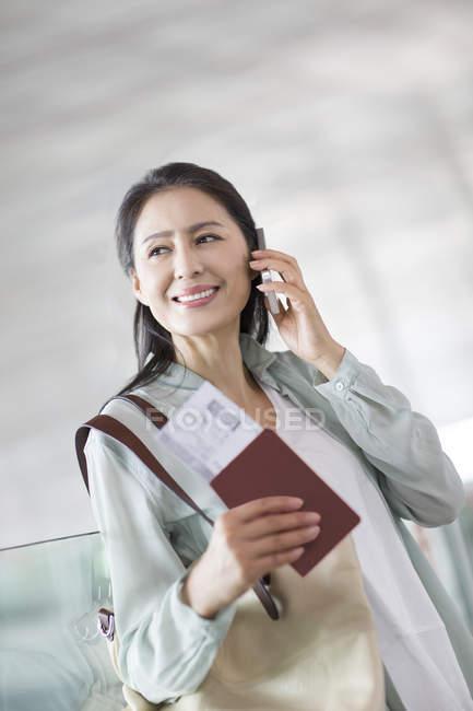 Reife Chinesin Telefonieren am Flughafen — Stockfoto