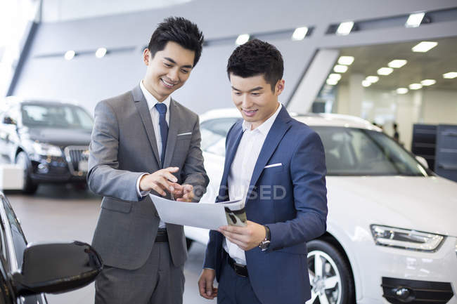 Chinese businessman making deal with car seller in showroom — Stock Photo