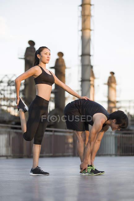 Couple of athletes stretching on street — Stock Photo