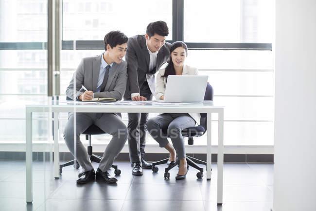 Empresarios chinos usando laptop en reunión - foto de stock