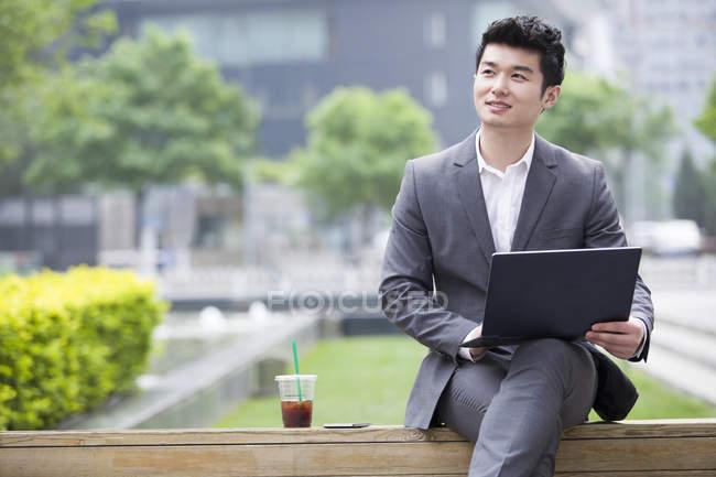 Uomo d'affari cinese che lavora con il computer portatile sulla panchina stradale — Foto stock