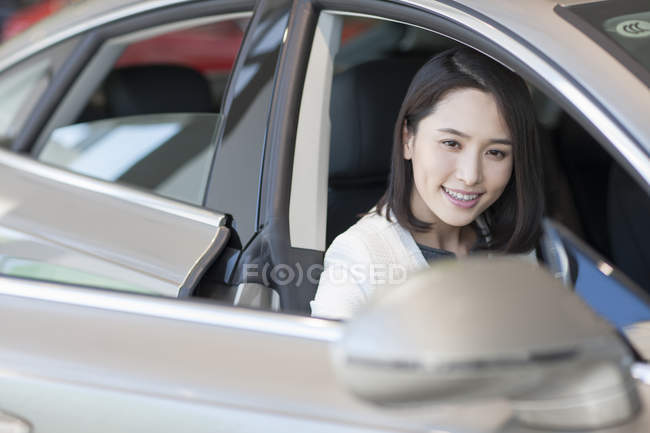Young chinese woman sitting in car — Stock Photo