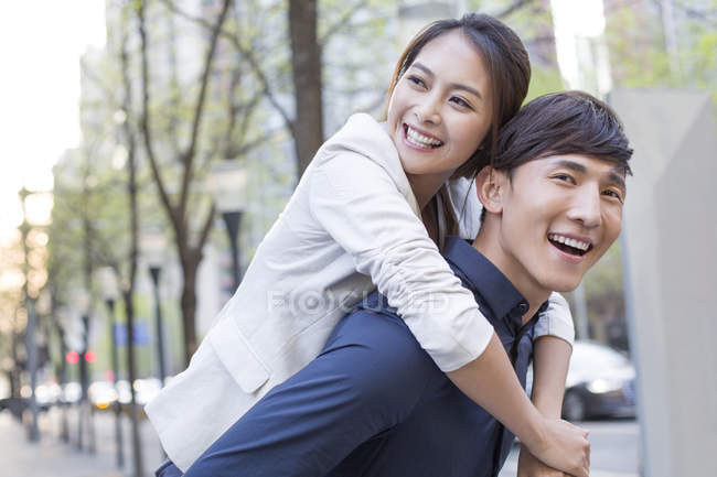 Chinese man holding piggy back girlfriend on street and laughing — Stock Photo