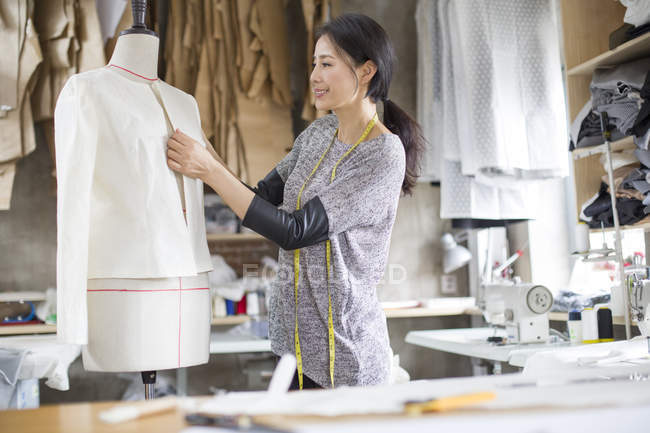 Chinese fashion designer working in studio with mannequin — Stock Photo