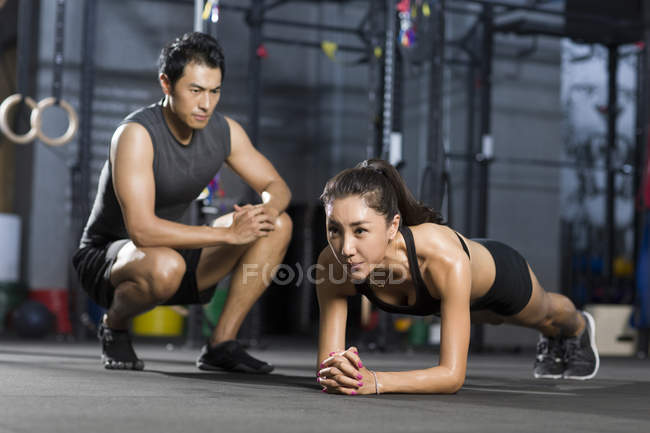 Chinese woman doing push-ups with trainer in gym — Stock Photo