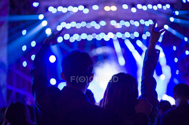 Chinese couple making rock and roll sign at concert — Stock Photo