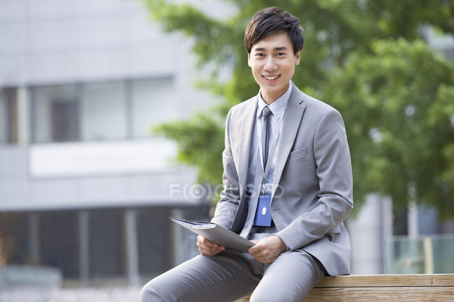 Chinese businessman sitting on bench with fold — Stock Photo