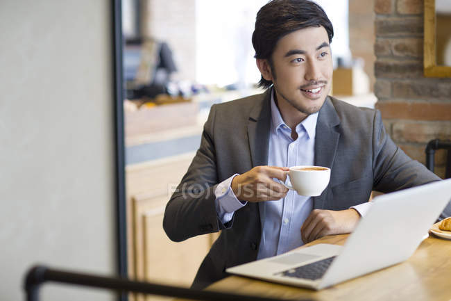 Uomo d'affari cinese che si siede con il laptop in caffè e caffè — Foto stock