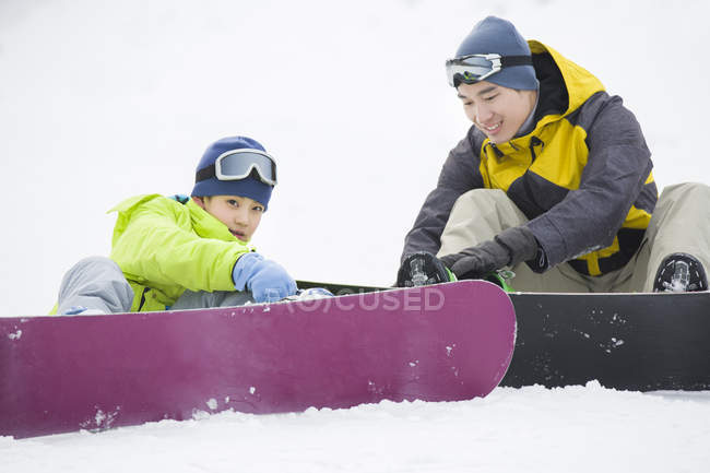 Chinese father helping son wearing snowboarding gear on snow — Stock Photo