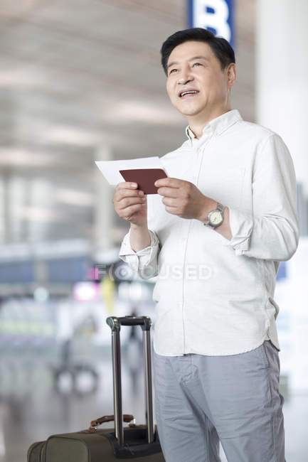 Mature chinese man waiting at airport with ticket — Stock Photo