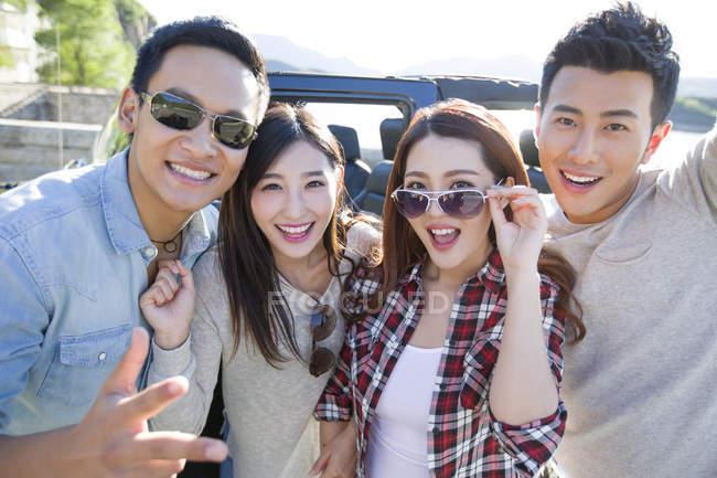 Amici cinesi in posa con auto in periferia — Foto stock