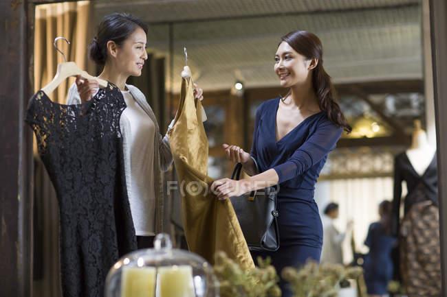 Matura cinese boutique proprietario aiutare il cliente a scegliere il vestito — Foto stock