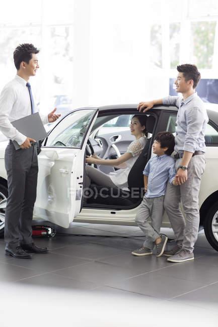 Китайський автомобіль продавець допомоги сім'ї виборі автомобіль в автосалоні — стокове фото