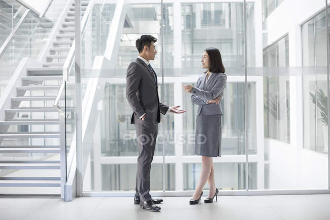 Chinese business people talking in office building — Stock Photo