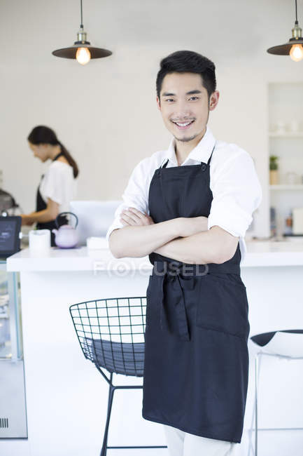 Chinese coffee shop owner standing with arms folded — Stock Photo