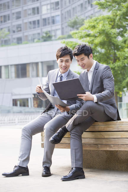 Китайских коллег, работающих с ноутбуком на улице — стоковое фото