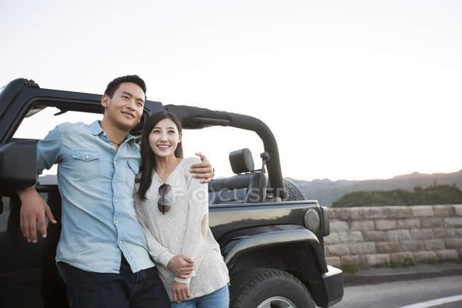 Китаєць обійматися жінка перед автомобілем — стокове фото