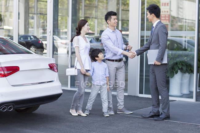 Familia china estrechando la mano con el vendedor de coches en frente de la sala de exposición - foto de stock