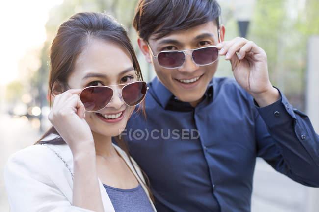 Casal chinês posando com óculos de sol — Fotografia de Stock