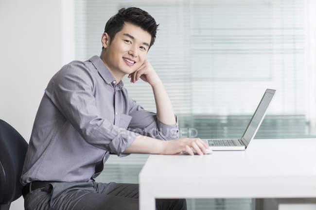 Homme d'affaires chinois assis avec ordinateur portable au bureau — Photo de stock
