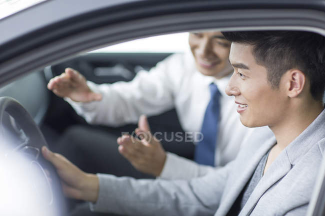 Car dealer helping man with test drive — Stock Photo