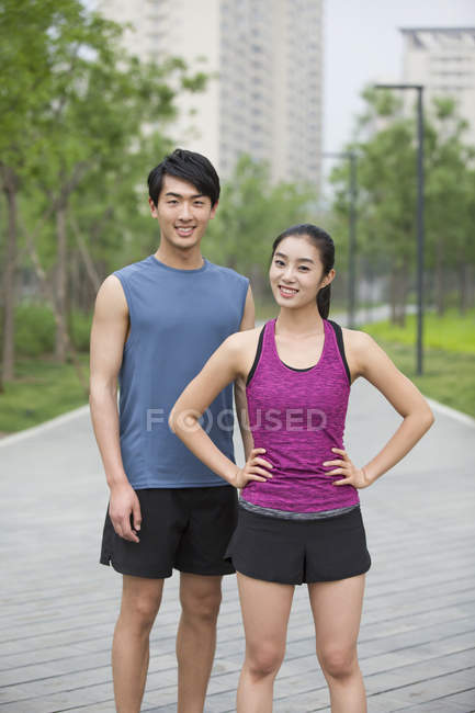 Pareja China de corredores de pie en la calle y sonriendo - foto de stock