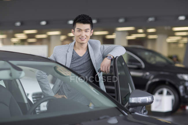 Chinese man posing with car on parking lot — Stock Photo