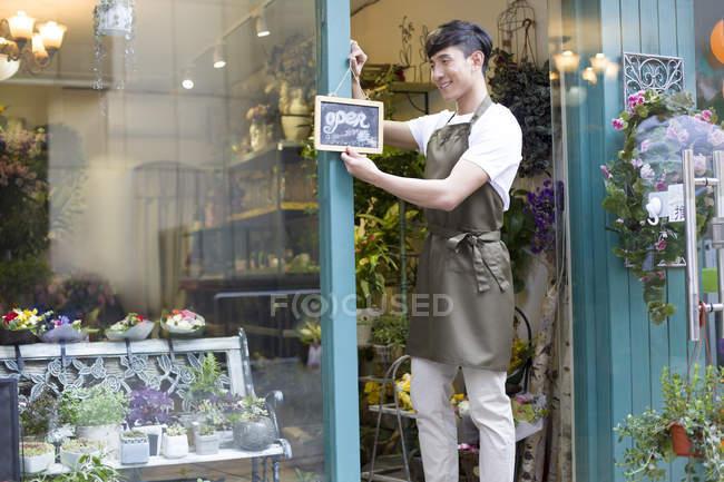 Китайский флорист вешает открытую табличку на дверь магазина — стоковое фото