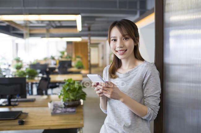 Donna cinese che tiene smartphone e che sorride nell'ufficio — Foto stock