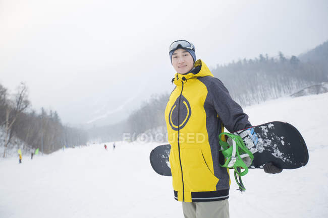 Chinese man posing with snowboard on snowy slope — Stock Photo