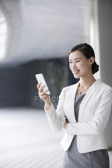 Donna di affari cinese che tiene smartphone e sorridere — Foto stock