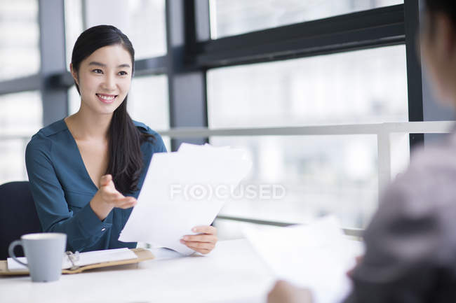 Chinese businesswoman sitting on meeting with documents — Stock Photo