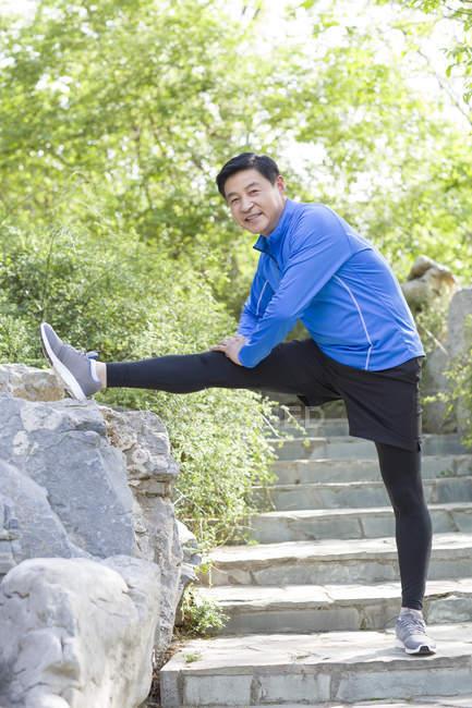Зрелый китаец, растянувшийся в парке — стоковое фото