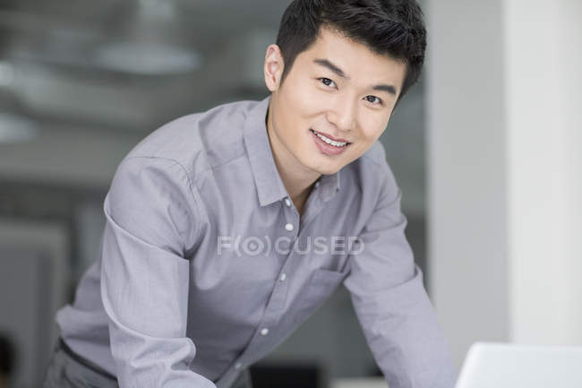 Chinese businessman leaning on table and looking in camera — Stock Photo