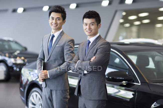 Chinese salesmen standing with in showroom — Stock Photo