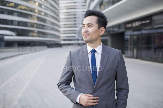 Chinese businessman looking at view and smiling — Stock Photo