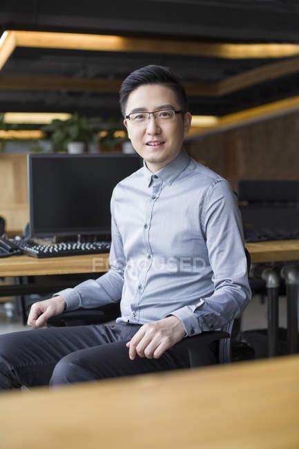 Chino masculino IT trabajador sentado en silla en el lugar de trabajo - foto de stock