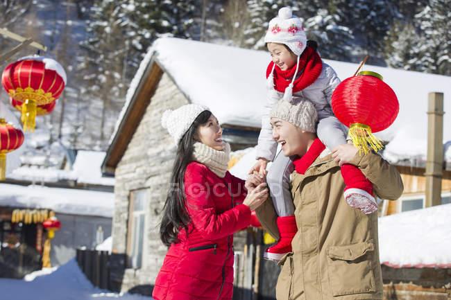 Китайський батька, несучи дочка з ліхтар на плечі при матері дивляться — стокове фото