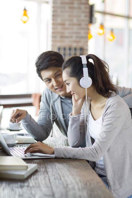 Uomo cinese e donna usando il portatile nella caffetteria — Foto stock