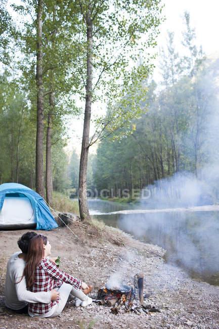 Coppia cinese seduta accanto al falò nella foresta — Foto stock